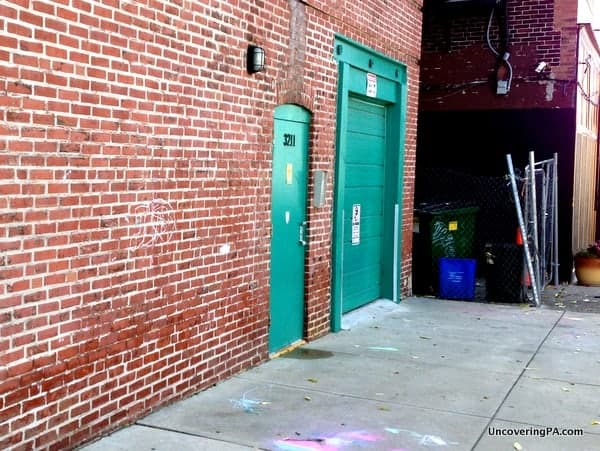 Behind a green door and a red brick wall sits the workshop of Peg and Awl.
