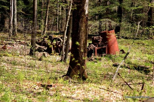 Rusty oil equipment sits next to the trail on the way to Miller Falls in Oil Creek State Park.