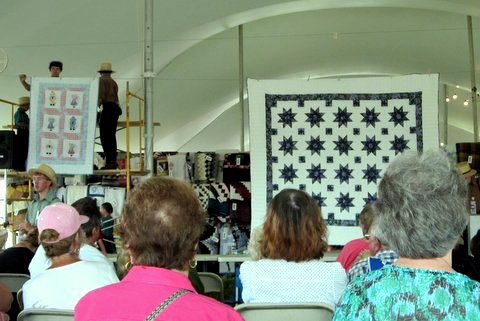 Quilts available for sale at an Amish Mud Sale in Lancaster County, PA.