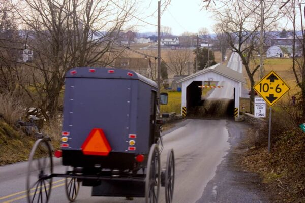 An Amish buggy rides towards Leaman's Place Covered Bridge in Lancaster County Pennsylvania