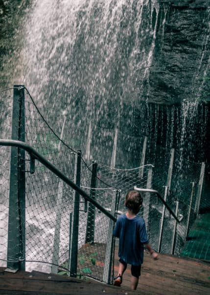 Child walking path behind waterfall at Buttermilk Falls in Indiana County PA