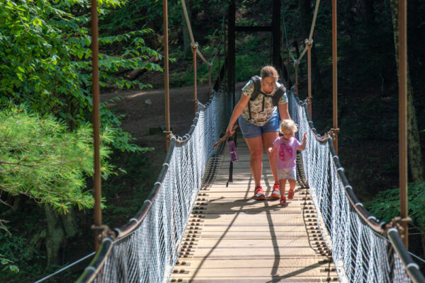 Child walking across the Swinging Bridge in Cook Forest State Park in Cooksburg PA