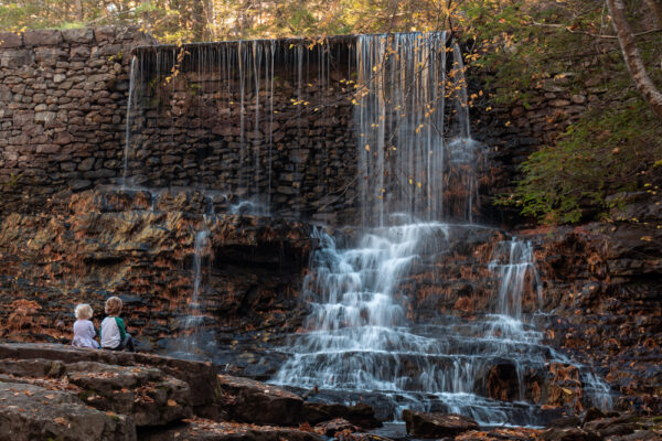 Kids sitting at a waterfall on the Shades of Death Trail at Hickory Run State Park in the Poconos of Pennsylvania