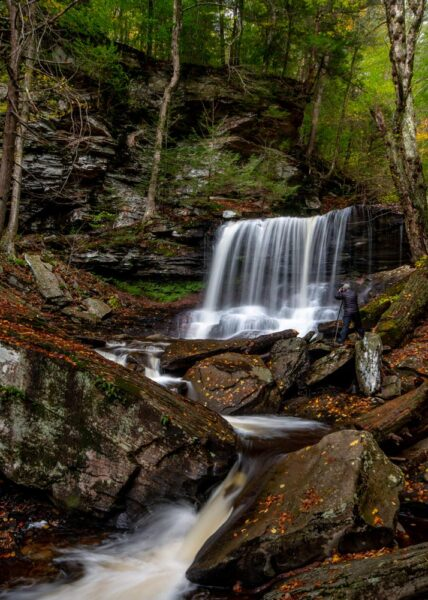 Man photographing a waterfall at Ricketts Glen State Park