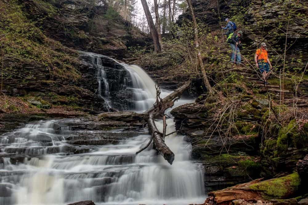 People walking down the side of a waterfall at Ricketts Glen State Park in Pennsylvania