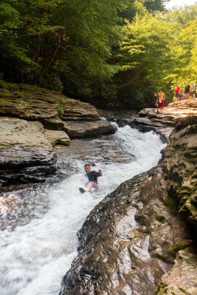 Person going down the Natural Waterslides in Ohiopyle State Park in PA