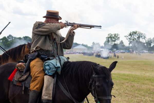 A Confederate cavalry soldier fires during the reenactment of the Battle of Gettysburg
