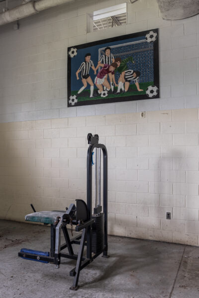 Weight equipment sits in front of an athletic mural inside the gymnasium at SCI Cresson