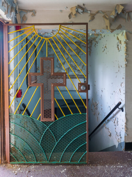 Colorful metal door with a cross at the abandoned Cresson Prison in Pennsylvania