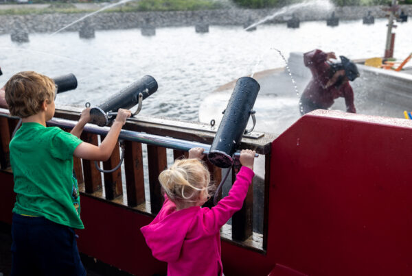 Kids shooting water cannons at a pirate in the Scallywags Cruise in Erie PA