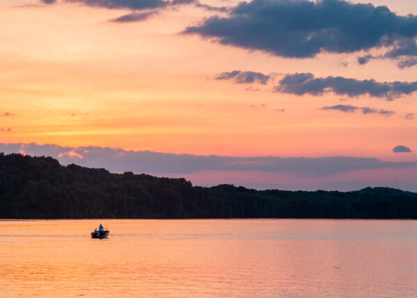 A boat on the waters of Lake Arthur in Moraine State Park at sunset