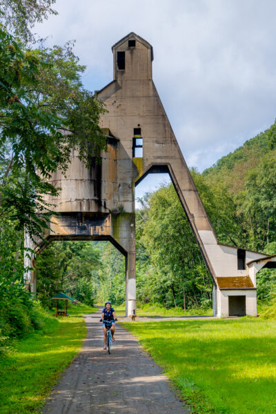 Woman riding a bike under a coaling tower on the Armstrong Rail Trail in Pennsylvania's Armstrong County