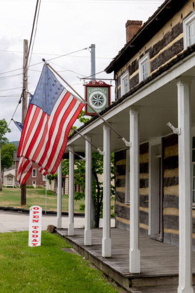 The front of the Compass Inn Museum near Ligonier, PA draped in flags
