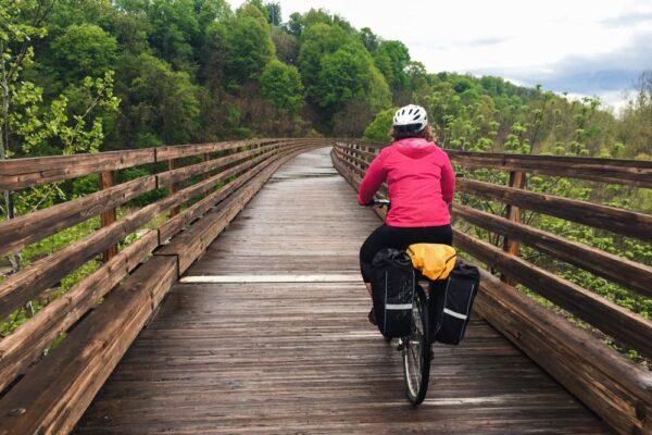 Woman biking over a bridge on a rail trail in Pennsylvania