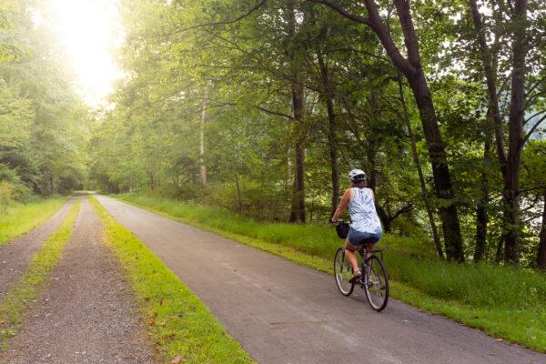 Woman biking on the Samuel Justus Recreation Trail at sunset