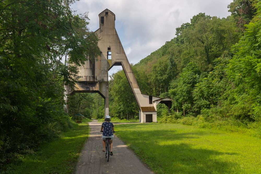 Woman biking the Armstrong Trail at the Coaling Tower Ruins