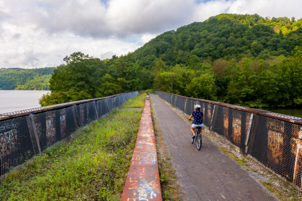 Woman on a bicycling crossing the bridge over the Redbank Creek on the Armstrong Trails.