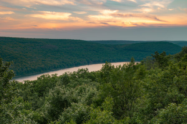 Sunset at Rimrock Overlook with trees and the Allegheny Reservoir in the distance.